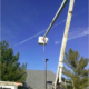 A crane is lifting a parking lot light into place.