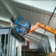 A fork lift lifts a cherry picker to the top of the mezzanine.